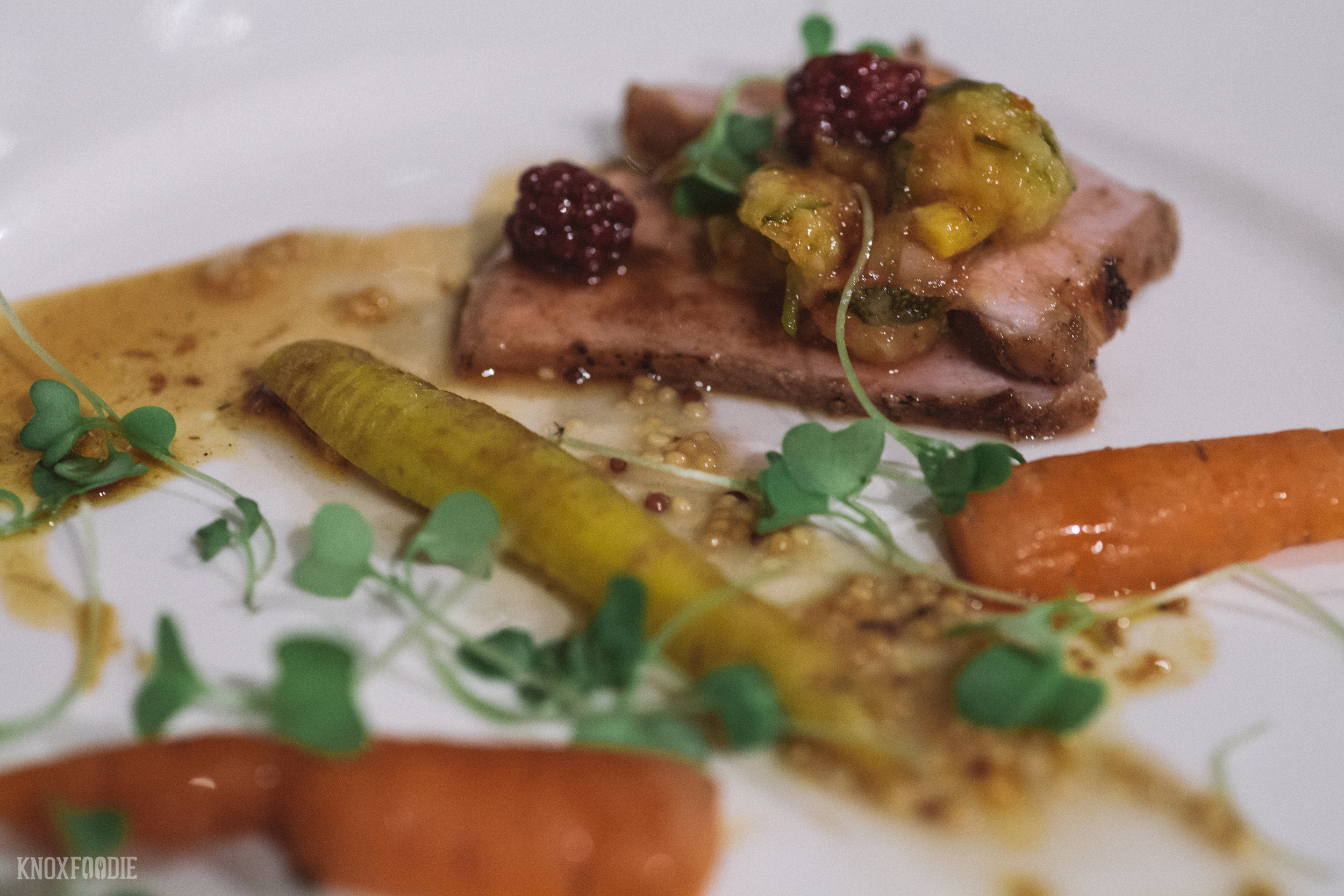 Charred pastured pork loin glazed with hickory bark sorghum syrup and WV salt, sassafras and wild ginger mustard, smoked carrot, poached blackberries, spicy pickled squash